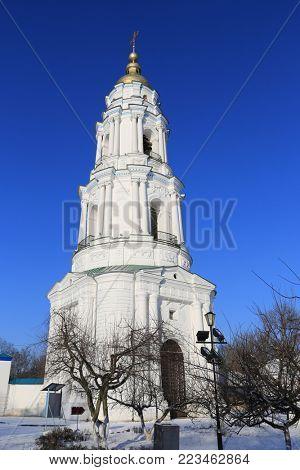 Bell tower Exaltation of the Cross Monastery on blue sky background. Poltava, Ukraine