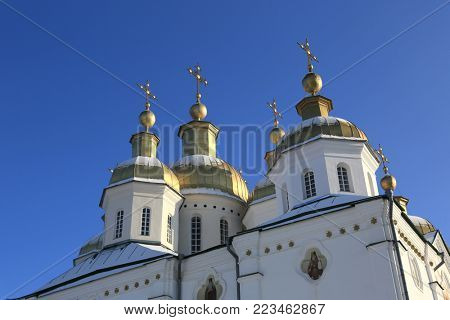 Cupola of Trinity Church Exaltation of the Cross Monastery on blue sky background. Ukraine, Poltava