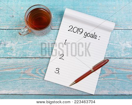 Notebook with new years resolutions for 2019 with a cup of thee and a pen on a blue wooden table seen from above