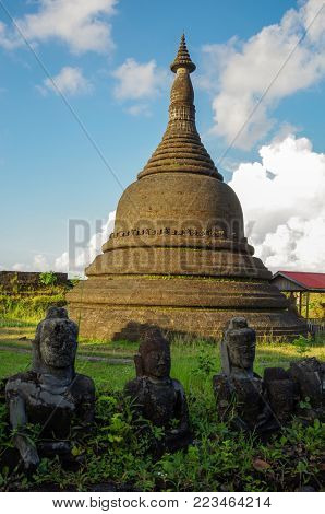 A stupa in the ancient heritage of Mrauk U, Myanmar in the back of smaller, damaged buddha statues