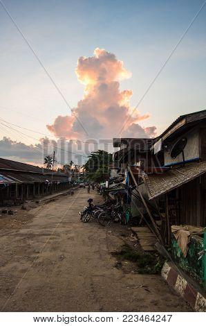 A normal, sandy street with shack buildings overshadowed by a huge monsoon cloud in Mrauk U, Rakhine State, Myanmar
