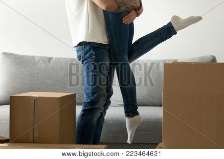 Happy couple starting new life together concept, loving man standing near boxes embracing woman lifting her up in the air excited about moving in, homeowners just moved into own home, close up view