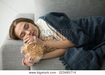Attractive girl sleeping on soft comfortable sofa with fluffy toy, beautiful lady lying asleep covered with plaid, childish immature woman dreamer holding favorite stuffed animal resting on couch