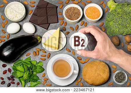 Food rich in vitamin B2. Various natural sources of vitamins. Useful food for health and balanced diet. Prevention of avitaminosis. Man's hand holds tag with name of vitamin B2. Top view