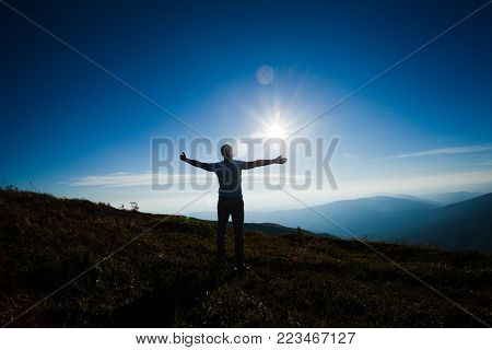 Silhouette of a person with hands up raised during the sunset on the top of the mountain