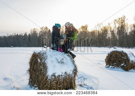 Two Cheerful Young Women On A Haystack.