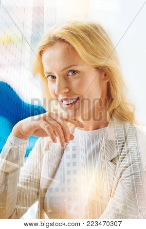 Positive glance. Portrait of charming woman looking at you with a smile while keeping her arm under her chin and having splendid mood