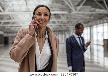 Good connect. Portrait of delighted attractive businesswoman is talking on smartphone with smile. She is standing in station building. Concentrated man is using mobile in background