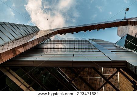 Up view on modern business office building and sky on the background. Urban exterior and tall perspective. Futuristic contemporary geometry construction
