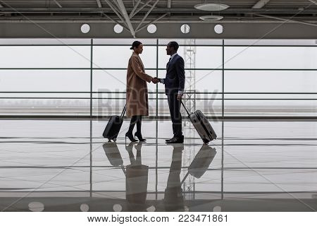 Full length of confident businessman is meeting his business partner at airport. They are standing with suitcases at lounge and shaking hands