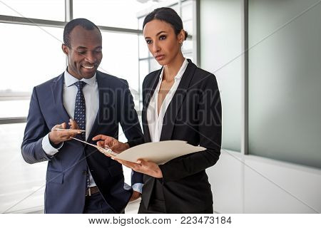 Important job. Pleasant elegant young professional business partners are standing in light office. Unsmiling gorgeous woman is holding papers while african man is looking at documents with smile