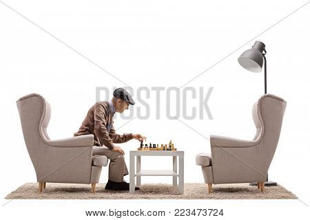 Senior seated in an armchair playing chess by himself isolated on white background