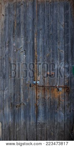 Wooden dark blue, blank, aged, peeled door for backdrop. Rusty latch on doorway. Close up, banner.