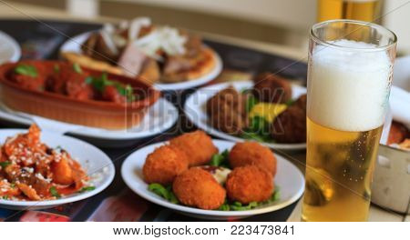Cold beer on tall glass with bubbles froth. Appetizers with blur food backdrop. Closeup, details