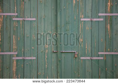 Wooden green door. Weathered blank, banner, background with rusty latch and padlock. Closeup, detail