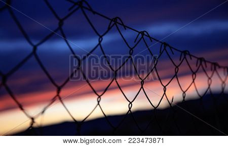 Wire mesh fence on silhouettes of poles with colorful sky blurred backdrop at sunset. Close up, detail, banner