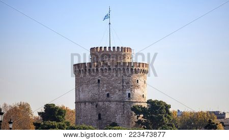 The White Tower in Thessaloniki, under Greece clear blue sky, is surrounding with trees.