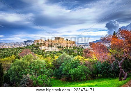 Acropolis with Parthenon. View through a frame of green plants, trees, ancient marbles and cityscape, Athens, Greece.