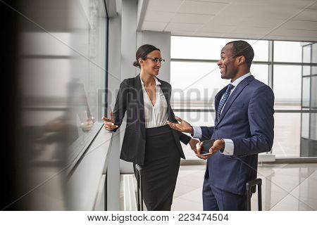 Successful project. Cheerful professional business partners are standing together at terminal lounge and discussing with smile. Man is gesticulating while holding mobile and looking at woman with joy
