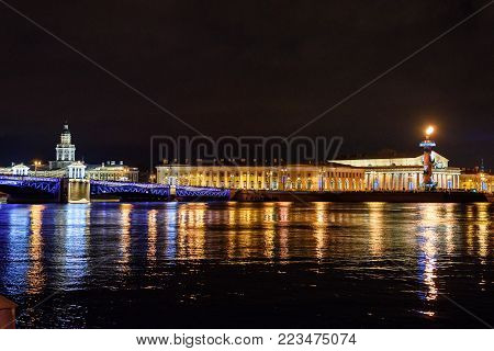 Palace Bridge and Vasilyevsky island Spit Strelka with Rostral columns at night. New Year and Christmas illumunated. Saint Petersburg, Russia