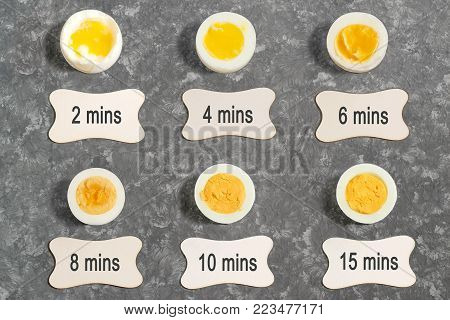 Cooking time and degree of readiness of boiled eggs. Boiled eggs in cut and label with time. Flat lay, top view