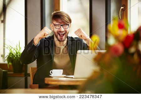 Emotional cheerful man celebrating with fists up at laptop in cafe.