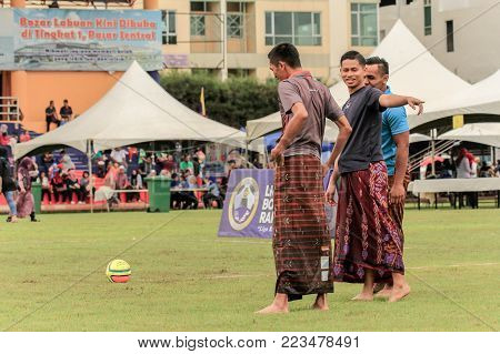 Labuan,Malaysia-Jan 18,2018:Group of man in traditional costume called sarongs ready to play football in Labuan,Malaysia.A sarong or sarung is a large tube or length of fabric worn in Southeast Asia.