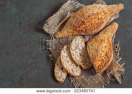 Freshly baked homemade whole wheat bread with flaxseeds (whole and slices) on coarse jute napkin. Useful dietary bread without yeast. Old iron knife. Greenish-brown textured background