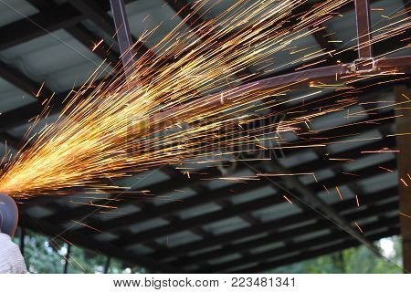 Sheaves of sparks while grinding a steel structure, grinder in action