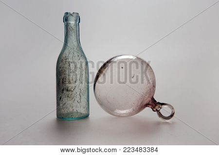 Antique vintage bottle of greenish color with mud on the walls and large glass bowl on the right on a light background, modern interior design of the wall.