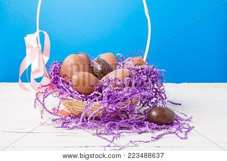 Photo of chicken , chocolate eggs, purple decorative paper in basket on empty blue background