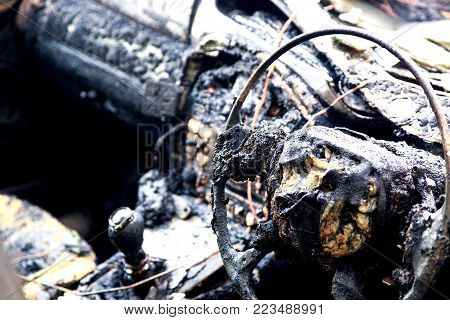 Inside of a burnt out car showing the remains of a steering wheel, gear stick and dashboard.