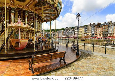 HONFLEUR, NORMANDY / FRANCE - MAY 23, 2013: Carousel in old village harbor. Calvados region. Europe.