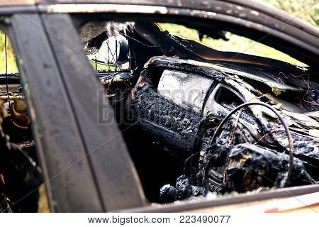 Looking Inside a burnt out car through a windown with no glass. Image showing the remains of the dashboard and steering wheel.