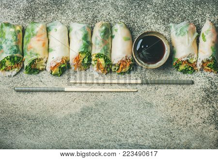 Helathy Asian cuisine. Flat-lay of vegan spring or summer rice paper rolls with vegetables, sauce and chopsticks over concrete background, top view, copy space. Clean eating, vegetarian, dieting food