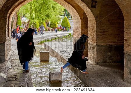 Isfahan, Iran - April 24, 2017: Two Iranian girls dressed in a black Muslim chador are crossing the stream of water under the bridge Allahverdi Khan, crossing the river Zayandeh.