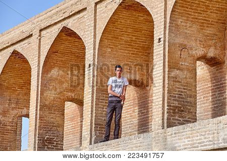 Isfahan, Iran - April 24, 2017: In arched niche of Allahverdi Khan bridge stands iranian teenboy in T-shirt with print including text with names of American cities New York, Los Angeles, and Las Vegas