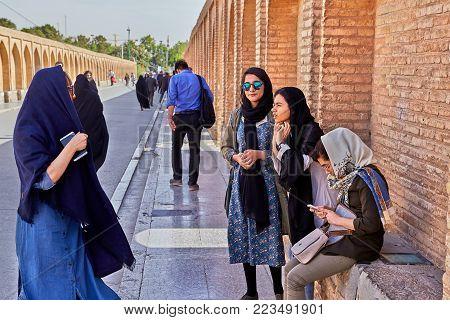Isfahan, Iran - April 24, 2017: Four young Iranian girls rest on the bridge Allahverdi Khan.