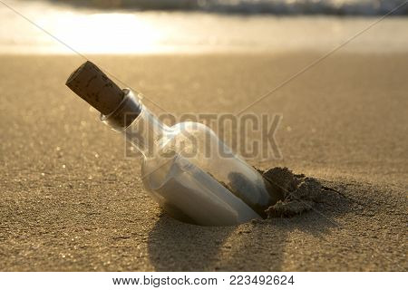 Message in a bottle half-buried in sand