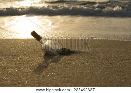 Message in a bottle half-buried in sand by the shore