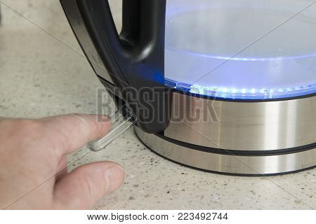 Finger pressing the power switch of an electric kettle