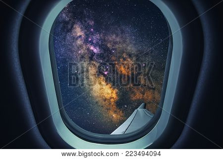 Airplane is flying at night. Space Milky Way view from plane window. Dark clear starry sky