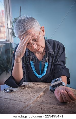 Worried senior lady having a headache and a bad blood pressure