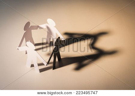 closed joining of four paper figure with black figure in hand down posture on light background. in concept of cooperation, weakness, fake and corruption.