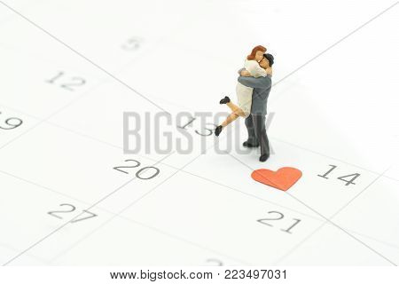 Couple Miniature 2 people standing on Calendar. Day 14 meets Valentine Day with Heart shaped red paper. Red heart is the promise of love. using as background Valentine concept with copy spaces for you