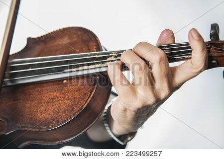 Closeup of a senior lady's finger playing the violin