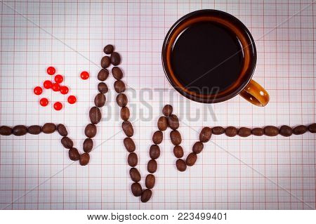 Electrocardiogram line of roasted coffee grains, cup of hot coffee and supplement pills on graph paper, ecg heart rhythm, health care concept
