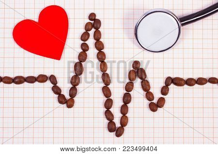 Electrocardiogram line made of roasted coffee grains, medical stethoscope and red heart on graph paper, ecg heart rhythm, medicine and healthcare concept