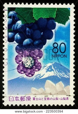 Moscow, Russia - January 24, 2018: A stamp printed in Japan shows bunch of grapes, jewelry and mountain Fuji, series