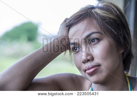 dramatic portrait of sad and thoughtful young beautiful Asian woman on her 20s or 30s looking away outdoors pensive and sad in feeling and facial expression concept
